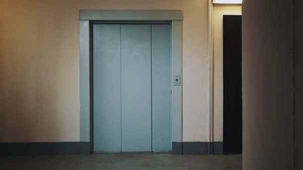Lift In Huis : Guy lopen uit lift met koffer in slaapzaal huis corridor