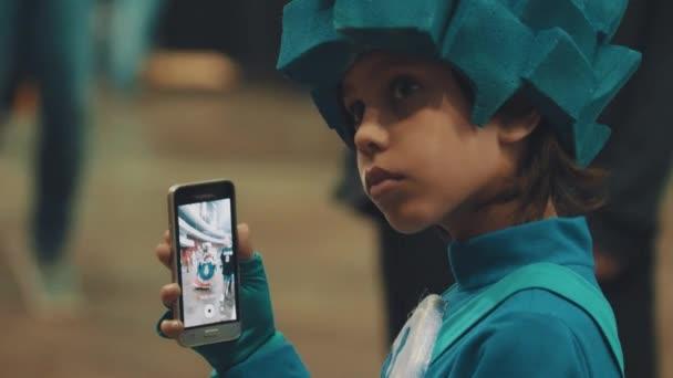 Petrohrad, Rusko - 20 května 2017: Young kluk modrý znak kostýmu natáčení taneční lidí na chytrý telefon