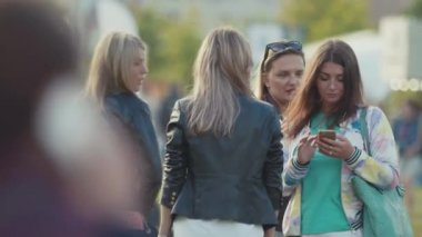 SAINT PETERSBURG, RUSSIA - JUNE 24, 2017: Young girls group talking and texting on smart phones at crowded city park