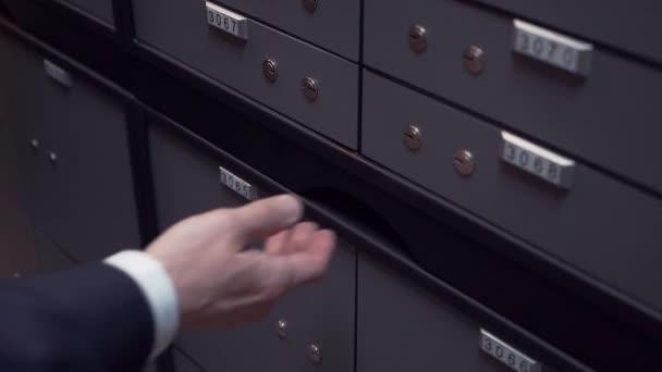 Bankovní manažer rukou vytáhnete skládací stůl v nouzovém depozitáře pro klienta
