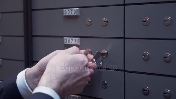 Bankovní manažer ruce s klienta stařec zamykání bezpečné buňky pomocí dvou klíčů