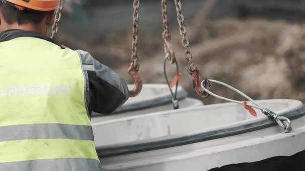 Worker in hard hat put chains in metal noose on concrete chamber manhole ring