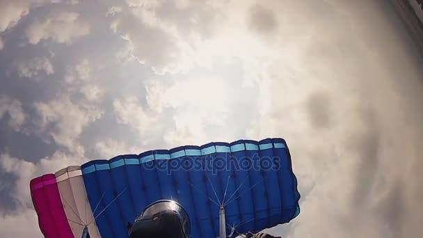 Parašutista v helmě, létání na padáku v obloze. Výška. Extrémní sport. Rychlost