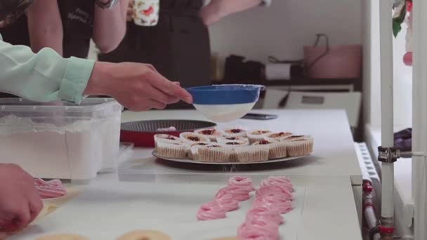 Woman pastry chef in apron sifts powdered sugar through sieve on merengues
