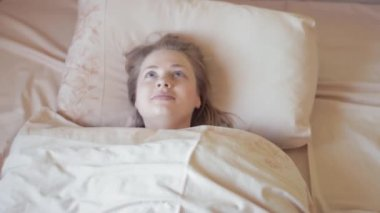 Attractive fresh looking blonde woman lying in bed in early morning