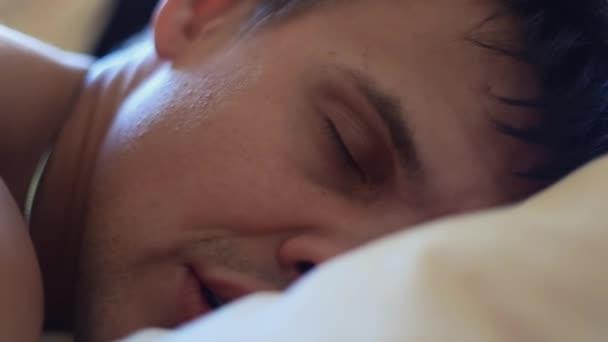 Svalnatý muž spí v posteli hlavou na polštář v časných ranních hodinách