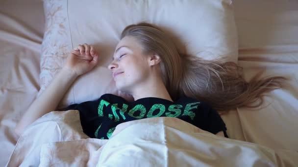 Atraktivní líná blond žena leží v posteli v časných ranních hodinách