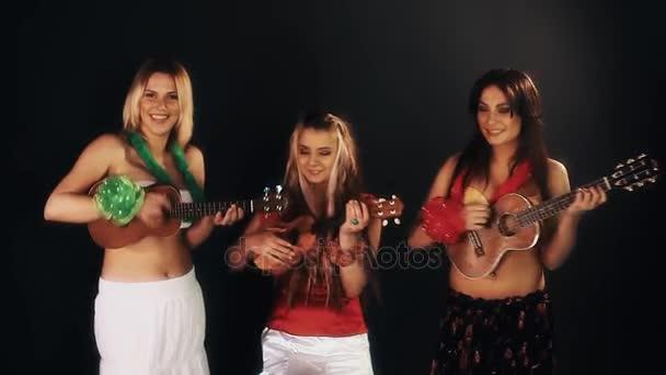 drei attraktive, fröhliche Frauen in hawaiianischen Kleidern, die Ukulele spielen
