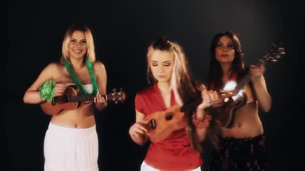 drei hübsche fröhliche Mädchen in hawaiianischen Kleidern, die Ukulele spielen