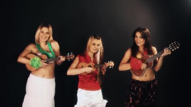 drei attraktive, gut gelaunte Frauen in hawaiianischen Kleidern, die Ukulele spielen