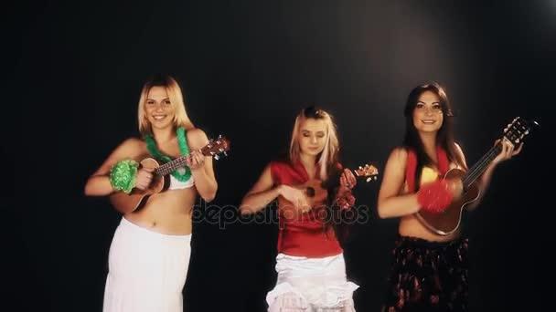 drei hübsche, gut gelaunte Frauen in hawaiianischen Kleidern, die Ukulele spielen