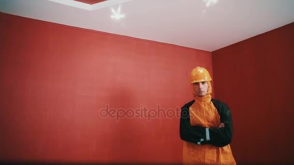 Man in hazard jacket and hard hat cross armed in red room, looking into camera