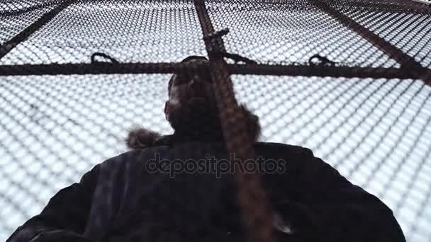 Mladý vousatý chlap v zimní bundě za drátěný plot