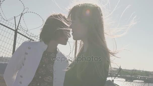 Krásné mladé dívky pár na střeše s výhledem na řeku malebné město