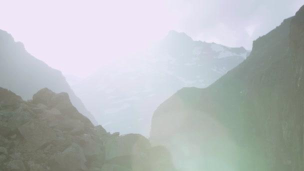 Rychlá řeka peřeje v kamenité hory pod sněhem s zelené keře