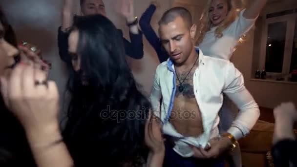 Playboy man unbuttons white shirt at party in living room with sexy girls around