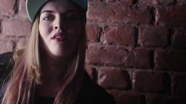 Blonde girl in hip hop snapback posing in front of brick wall in dark room