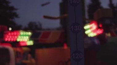 Height meter scale at amusement park attractions with flashing colorful light
