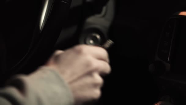 Male hand puts car key into socket and starts engine