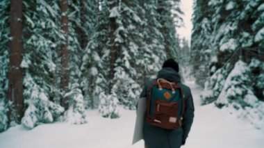Young man walking on snow covered trail in forest on winter day