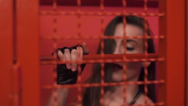 Young sexy girl in red cage and leather gloves teasing dancing