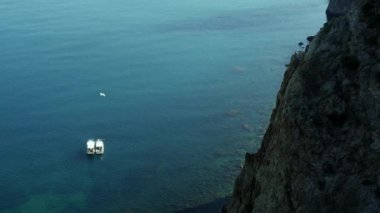 Beautiful view of boats in calm blue ocean from cliff