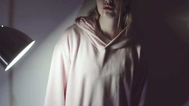 Mladá atraktivní žena s třpytky na obličej stojící u zdi v temné místnosti