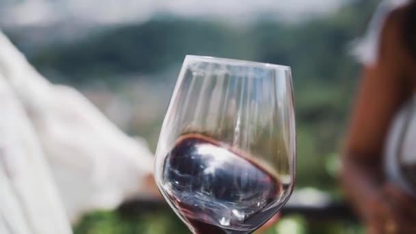 Hand einer erwachsenen Frau schüttelt Glas Rotwein