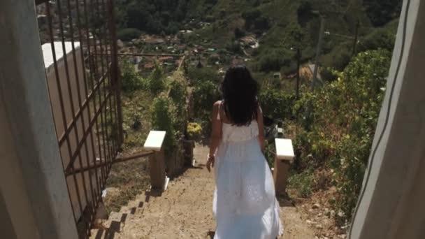 Mladá žena v bílých šatech stojící pěší schody Vila v horách, města na pozadí