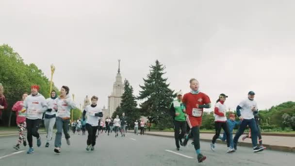 Kids and adults running crowd of people in sportive clothes on m