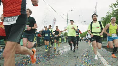 Cheerful athletes running marathon on wet asphalt covered in con