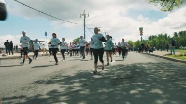Group of joggers running marathon in colorful sportive clothes