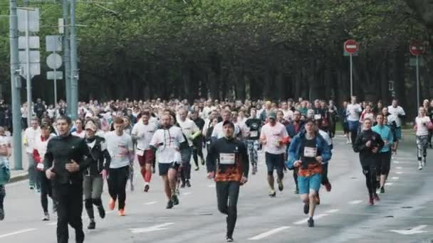 Huddle of sportive joggers running marathon on road at city park