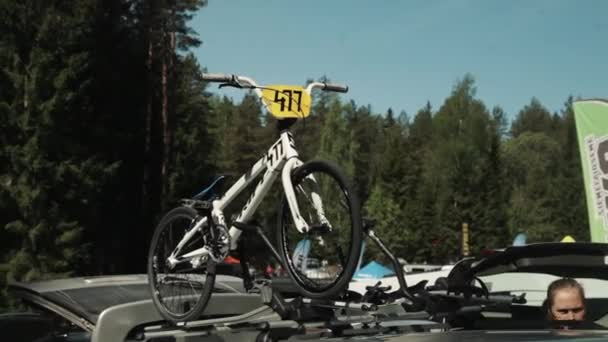 White racing bicycle straped on car roof at parking lot in fores