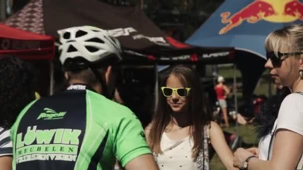 Dívka v sluneční brýle s rodinou sdělí sportovec v helmě bic