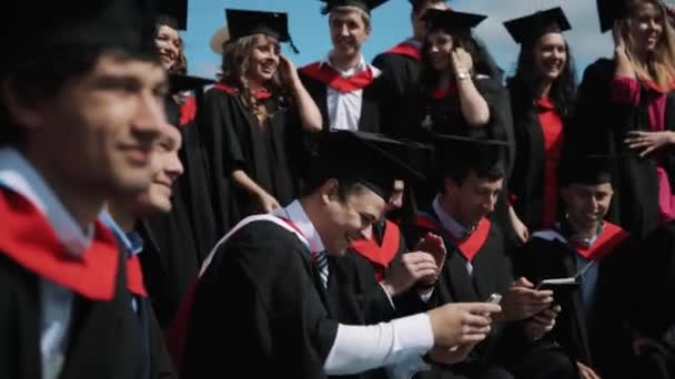 23a1aef0e0 Group of joyful students graduating posing for photo outdoors in– stock  footage