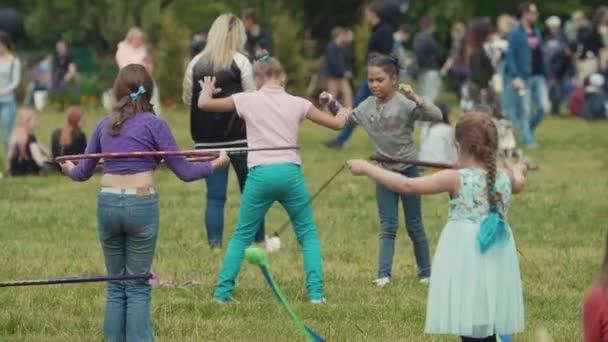 Kleine Mädchen in Zeitlupe spielen mit Hula-Hoop-Reifen und Luftbändern