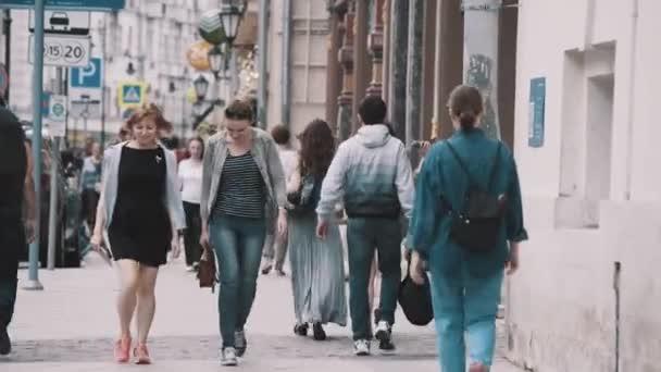 Women friends walking with people crowd on city streets