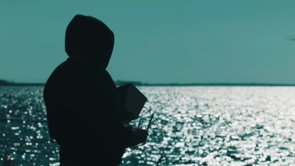 Silhouette of man in hood catching flying quadcopter on lake shore