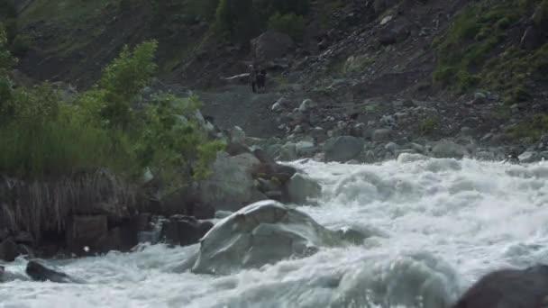 Dva muži na rychlá řeka peřeje ve vysokých Skalnatých hor pokryté zelené keře
