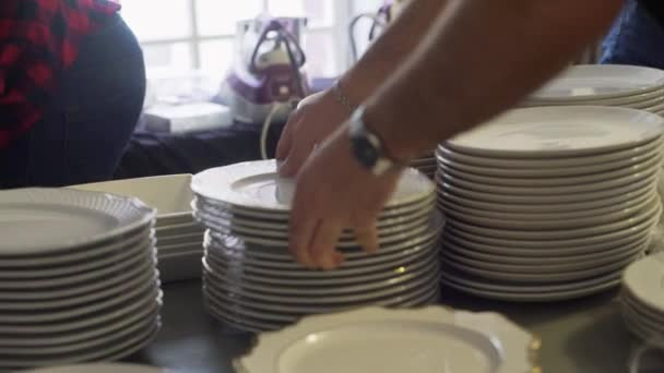 Proces několika párů rukou dát svazek bílých talířů na tmavý stůl