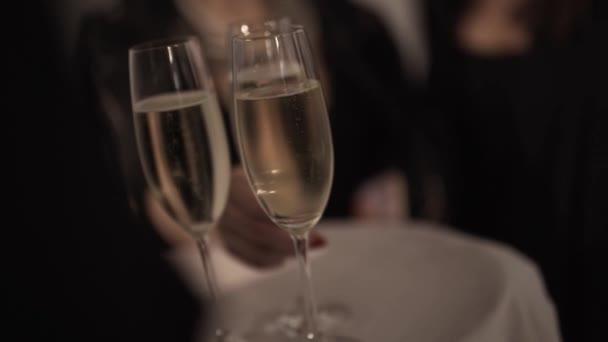 Rozmazaný pohled na číšníka v černém podnosu se třemi sklenicemi šampaňského