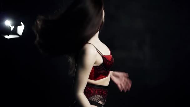 Woman stripper with long hair in tight red peignoir sexually moves on camera