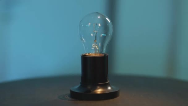 Camera is dynamically rotating around one bulb light placed on dark round table