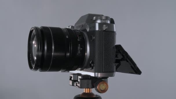 Bezzrcadlový fotoaparát fujifilm x-t3 se stavebnicovým objektivem 18-55 otáčejícím se 360 na stativu, na nutrálním šedém pozadí s čočkami a modrým kouřem.