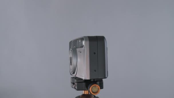 Régi hordozható karcos kompakt film kamera forgó 360 állvány tápanyagszürke háttér stúdióban.