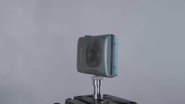 Régi hordozható karcos kompakt kánon kamera forgó 360 állvány tápanyagszürke háttér stúdióban.