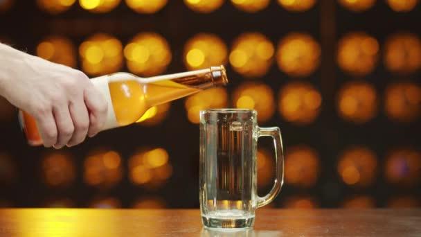 Mans kézzel öntött sört egy sörösüvegből az asztalon álló pohárba, hab kalap megy fel bokeh háttér.
