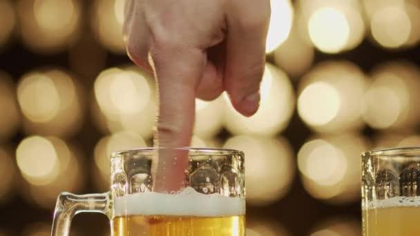 Mann steckt Finger in einen Bierkrug und macht Schaum, Bokeh Hintergrund Nahaufnahme.