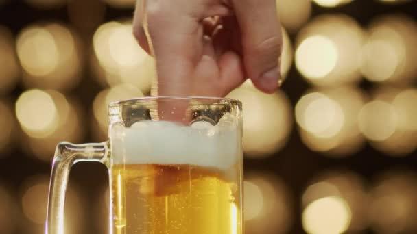 Kaukázusi férfi keveri hab egy ujj egy sör bögre bokeh háttér közelkép.